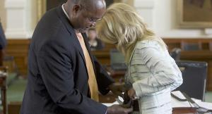 Sen. Rodney Ellis helps fellow senator, Wendy Davis put on a back support belt.