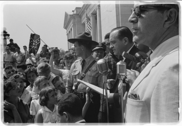 """Photograph shows a group of people, one holding a Confederate flag, surrounding speakers and National Guard, protesting the admission of the """"Little Rock Nine"""" to Central High School. Library of Congress Prints and Photographs Division Washington, D.C. 20540 USA – Photo Credit: John T. Bledsoe"""